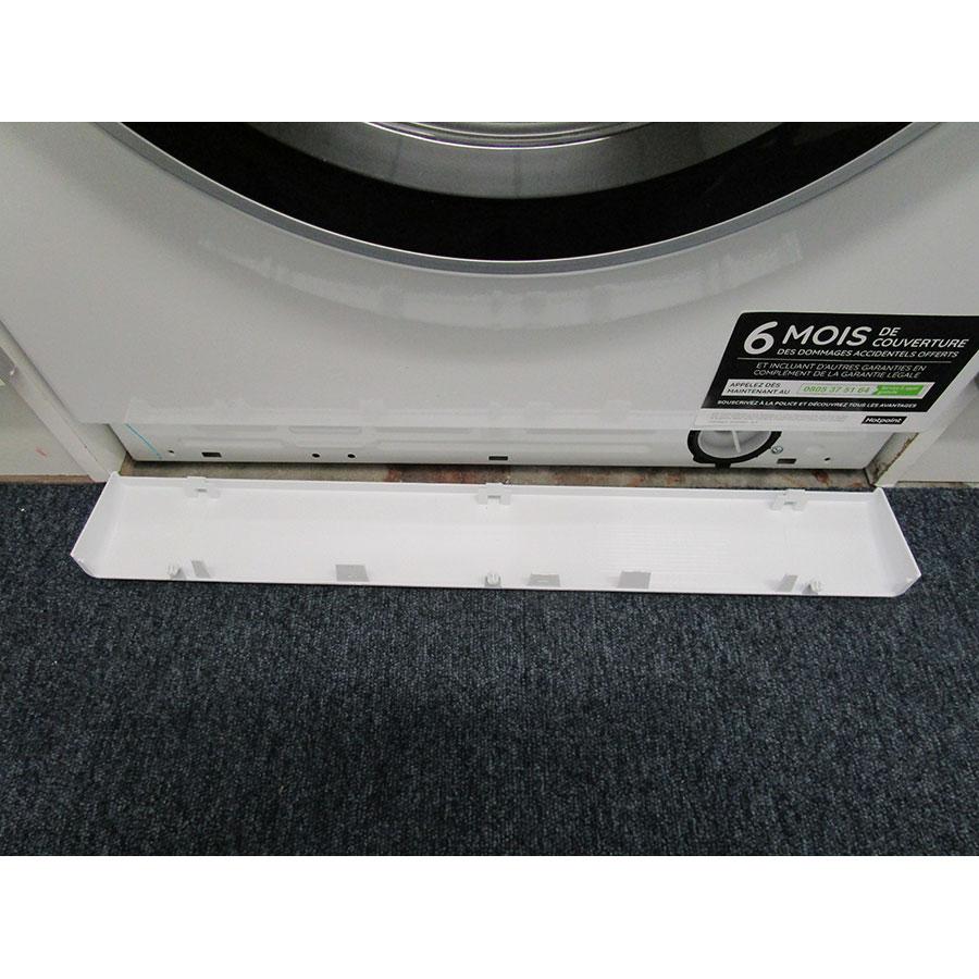 Hotpoint NM11946WSAFR - Ouverture de la plinthe masquant le filtre de vidange